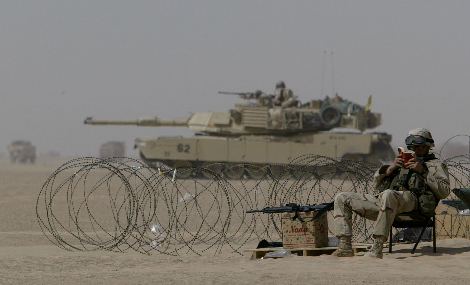 A US army infantry soldier reads a book as a M1A1 Abrams tank passes his back somewhere in the desert outside Kuwait City, March 13, 2003. REUTERS/Kai Pfaffenbach